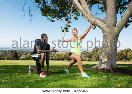 Young woman and trainer with lunge rope in park - Stock Photo
