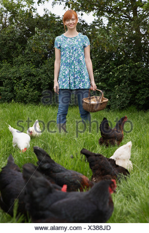 Woman holding egg basket by hens in garden, portrait - Stock Photo