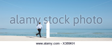 Man running on beach towards open door, rear view - Stock Photo