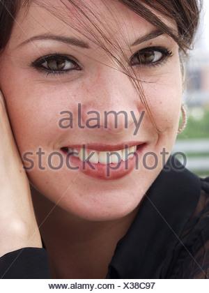 Laechelnde dunkelhaarige junge Frau - Stock Photo