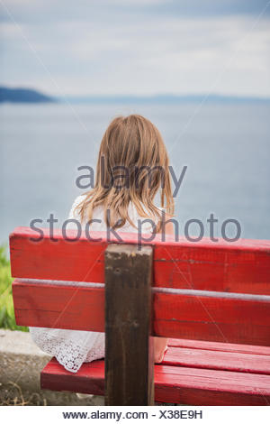 Girl sitting on a bench looking out to sea, Greece - Stock Photo