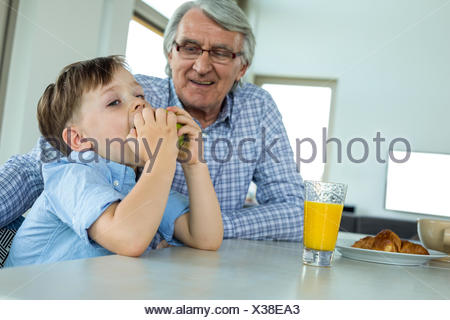 Grandfather and grandson having breakfast - Stock Photo