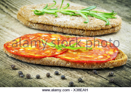 Sausage with bread and herbs on a wooden table - Stock Photo