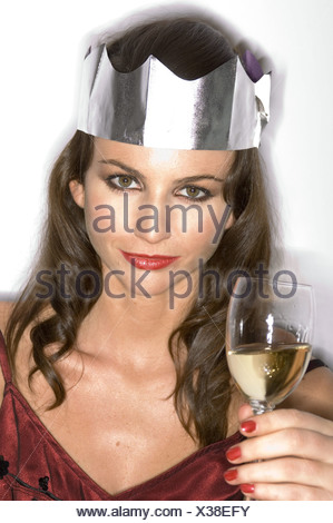 Female with brunette hair wearing dark red satin dress, silver paper hat, smokey brown eye make up Holding glass of white wine - Stock Photo