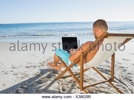 Relaxed handsome man working on his laptop - Stock Photo
