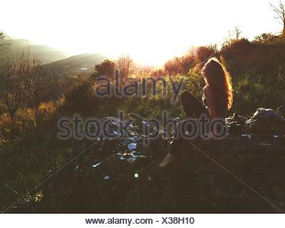 Side-View Of Young Woman Sitting On Rock - Stock Photo