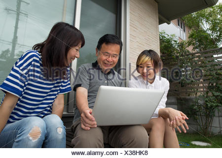 A man and two women sitting outside a house. Holding a laptop computer. - Stock Photo