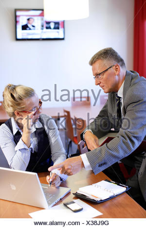 Man, 54 years, and woman, 40 years, during a business meeting - Stock Photo