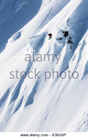 Professional Snowboarder Helen Schettini, catches air and grabs her board on a sunny day while snowboarding in Haines, Alaska. - Stock Photo