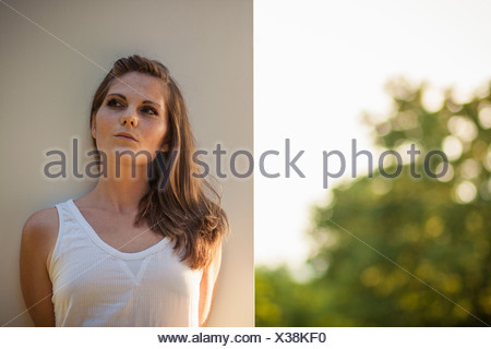 Woman leaning against wall outdoors - Stock Photo
