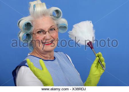 Elderly lady dusting - Stock Photo