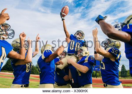 Teenage and young male American football team celebrating together on soccer pitch - Stock Photo