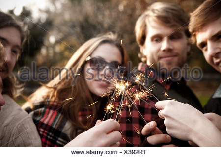 Friends holding sparklers - Stock Photo
