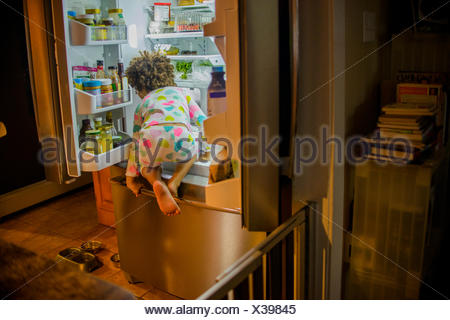 Rear view of girl sneaking food and drink from the refrigerator at night - Stock Photo