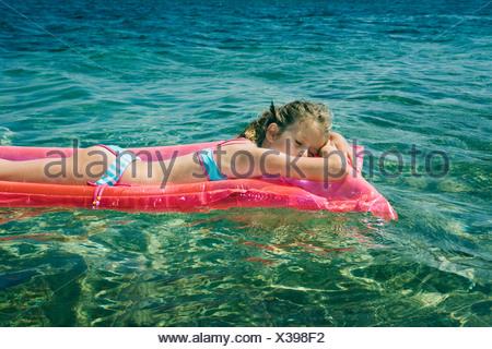Young girl sleeping floating on an inflatable raft. - Stock Photo