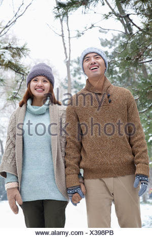 Young couple smiling in park in winter - Stock Photo