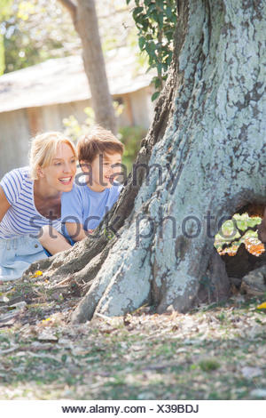 Young boy and mother hiding behind tree, playing hide-and-seek - Stock Photo