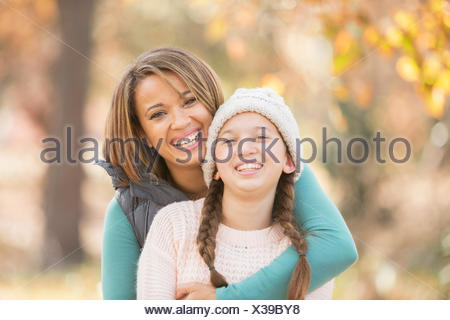 Portrait enthusiastic mother and daughter hugging outdoors - Stock Photo