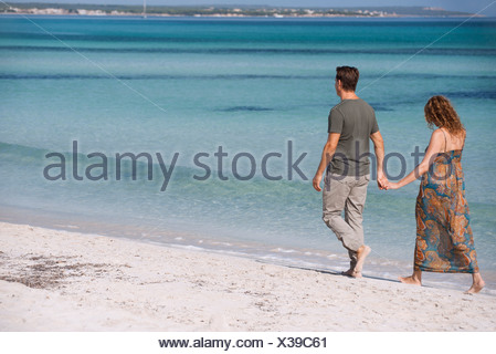 Could walking on beach holding hands - Stock Photo