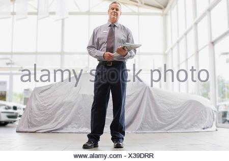Car salesman standing in showroom - Stock Photo
