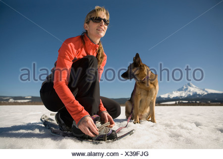 Young woman with dog puts on snowshoes near Mt. Hood, Oregon. - Stock Photo