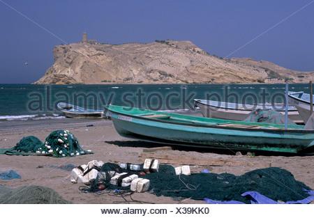 Oman middle East Al-Sawadi Beach fishing boats at Muscat coast beach sea ocean island watch tower nets Reg - Stock Photo