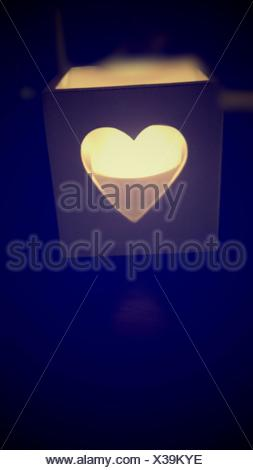Lit Candle In Heart Shape Box At Darkroom - Stock Photo