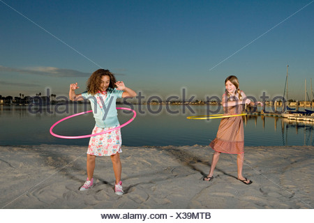 Girls playing with hula hoops - Stock Photo