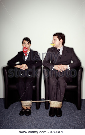Male and female business people gagged and tied - Stock Photo