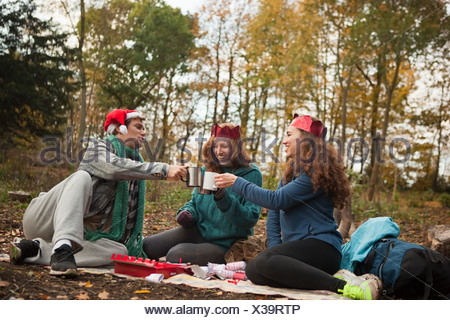Young friends wearing Santa hats and crowns toasting in forest - Stock Photo