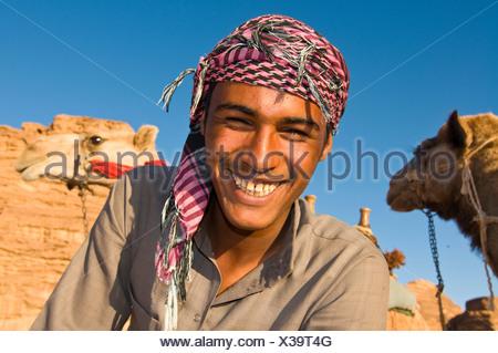 Smiling Bedouin man, portrait, with his camel, Wadi Rum, Jordan, Western Asia - Stock Photo