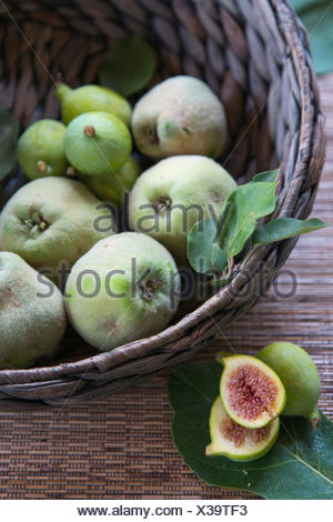 quinces and figs in woven basket with cut figs in foreground - Stock Photo