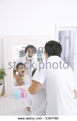 Father shaving with son standing beside - Stock Photo