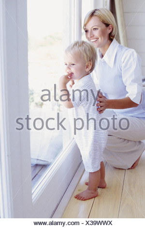 Toddler and mum looking out a window - Stock Photo