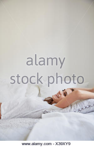 Surface view of beautiful young woman lying back on bed - Stock Photo