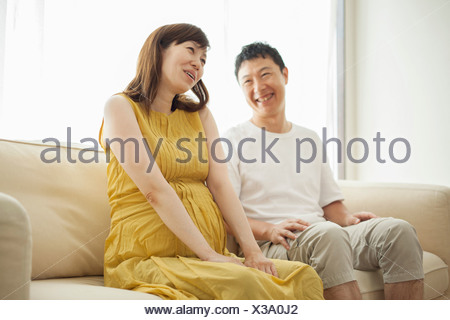 Man and pregnant woman sitting on sofa - Stock Photo