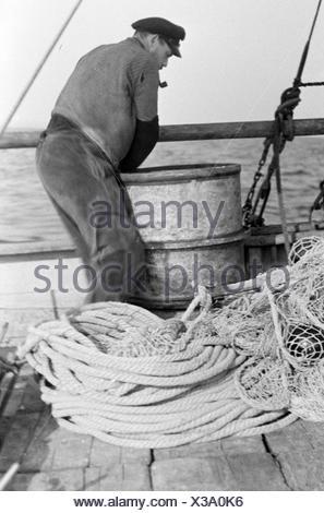 Ein Hochseefischer bei der Arbeit an Deck, Deutschland 1930er Jahre. A deep sea fisherman working on deck, Germany 1930s - Stock Photo