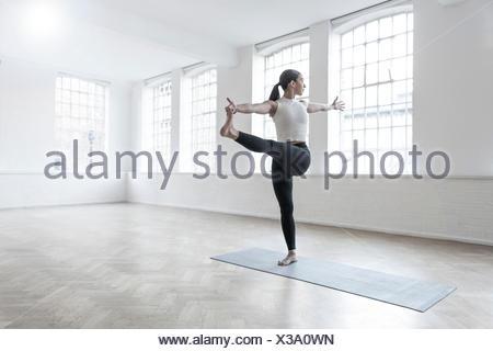 Woman in dance studio leg raised, stretching - Stock Photo