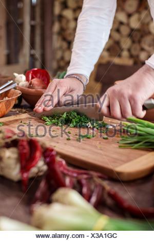 Unrecognizable person cutting parsley - Stock Photo