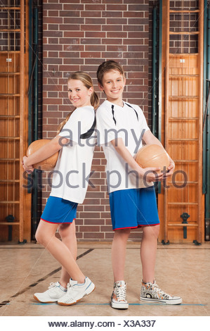 Germany, Emmering, Boy and girl (12-13) holding ball and smiling, portrait - Stock Photo