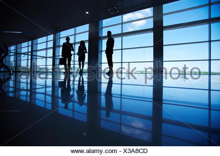 Silhouettes of several office workers standing by the window - Stock Photo