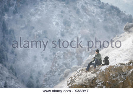 A man, a hiker in the mountains, taking a rest on a rock outcrop above a valley. - Stock Photo