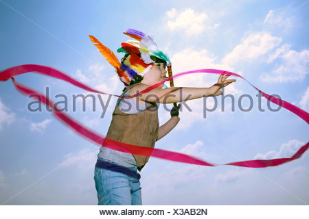 Toddler in Indian headdress with ribbon - Stock Photo