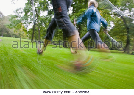 Motion studie of two nordic walker with sticks and sportive clothing walking on a green meadow in the English Garden in Munich - Stock Photo