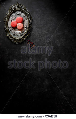 Macarons on a silver platter against a dark bckground - Stock Photo