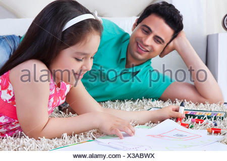Little girl drawing while lying by father on rug at home - Stock Photo