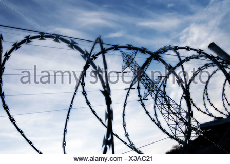 Electrical Tower with barbed wire barrier in the foreground against a blue sky with clouds - Stock Photo