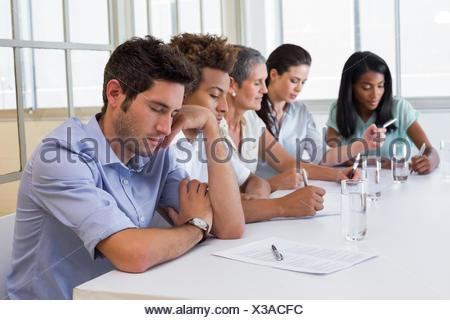 Casual businessman falling asleep during meeting - Stock Photo