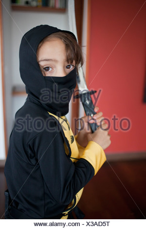 A boy dressed in a ninja costume holding a samurai sword - Stock Photo