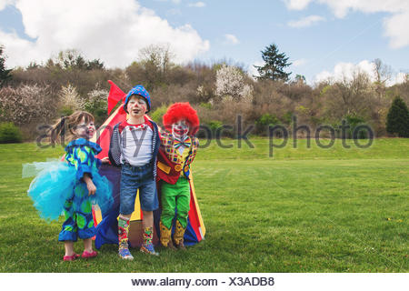 Three smiling children dressed as clowns - Stock Photo